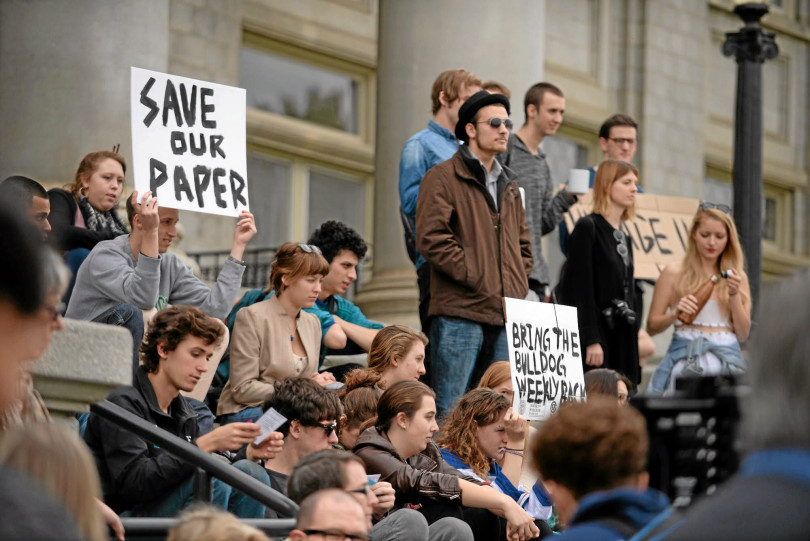 "About twenty students with signs saying ""Save our Paper"" and ""Bring the Bulldog Back."""