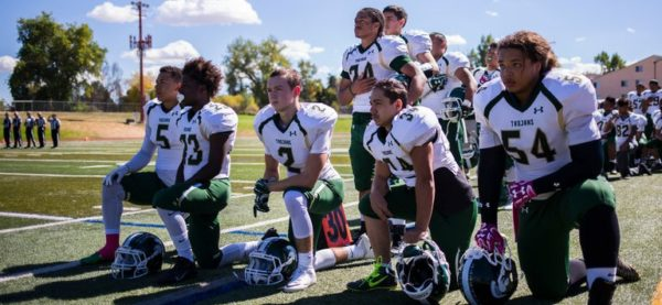 High school football players kneel during national anthem