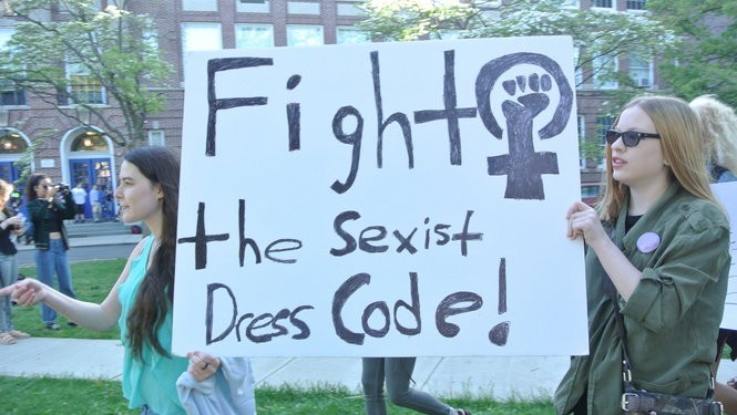 Two students with a banner reading fight the sexist dress code