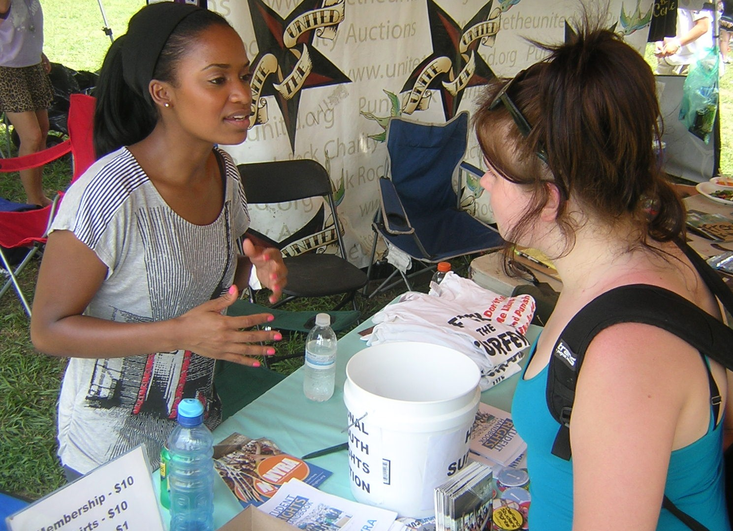NYRA volunteer speaking to another young person about youth rights during a tabling event