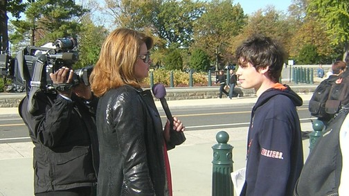 Reporter interviewing young person with camera and microphone