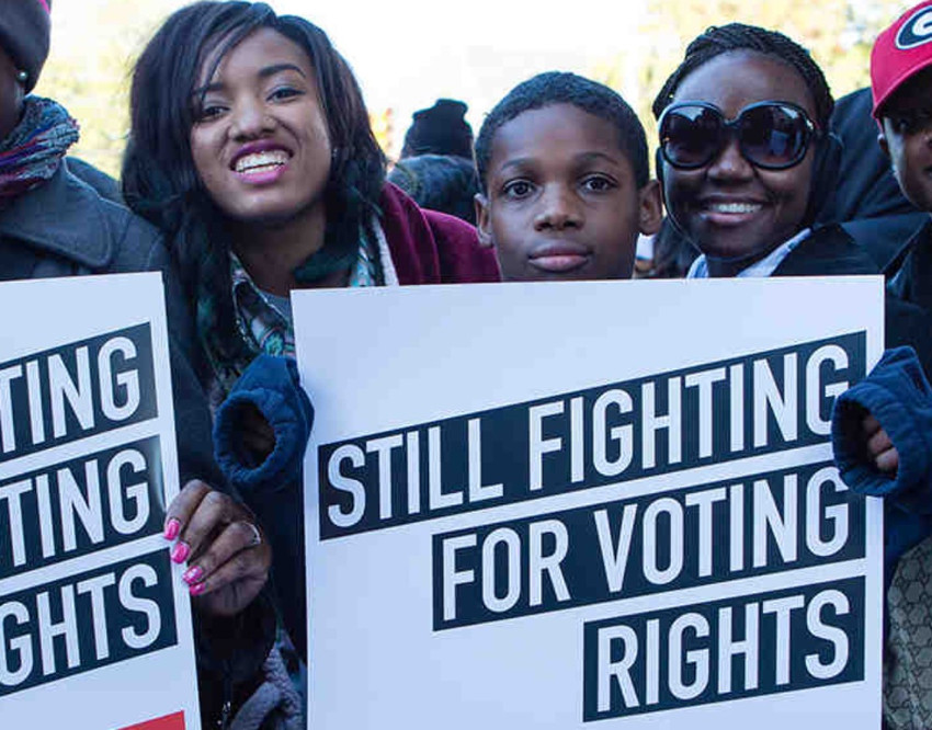 """Young black male holding a sign that reads """"Still fighting for voting rights"""""""